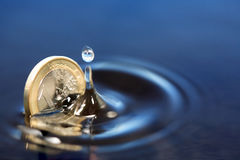 Sinking Euro Coin. Closeup of one euro coin sinking in water with splash Royalty Free Stock Photos