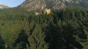 Sinking In Forest Castle Sunset Aerial 4k. Aerial footage of a beautiful castle in the Bavarian alps in Germany called Hohenschwangau. This is in 4k quality stock video