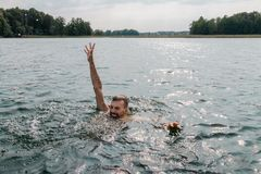 Drowning man. Sticking hand out of water royalty free stock photo
