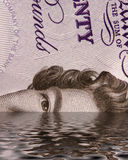 Sinking pound. Simulation of a UK twenty pound not sinking into sea. Concept of sinking pound in finance market Royalty Free Stock Images