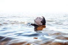 Sinking in the problems. Young man experiencing Royalty Free Stock Image