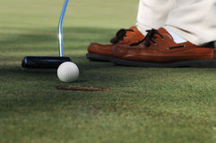 Sinking the putt. Worm's eye, close-up of golf ball, putter and golfer's shoes on a putting green Royalty Free Stock Photo