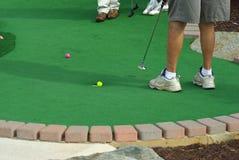Sinking a Putt. Golfer sinking a putt on a putt putt course Royalty Free Stock Photo