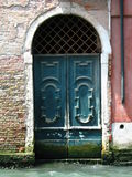 Sinking Venice. Doors in Venice and canal water stock images