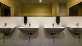 The sinks. Four sinks, thwo soap dispensers and a mirror wall in the public toilet stock photography