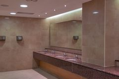 Sinks in a public toilet. With mirror and hand dryers Royalty Free Stock Photo