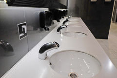 Sinks standing in a row. In a public restroom royalty free stock photography