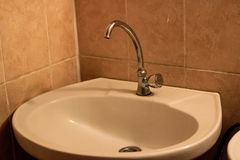 Sinks with a tap on the background of tiles. Close up royalty free stock photography