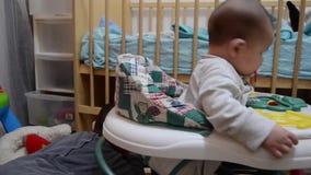 Sinlings играя совместно в их комнате, 2 летах старого мальчика играя с братом младенца в ходоке акции видеоматериалы