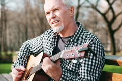 Sinnender reifer Mann, der Gitarre aufhebt lizenzfreies stockbild