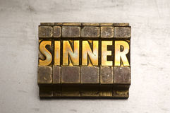 Sinner. Brass / Gold colored Sinner on silver metal background royalty free stock image