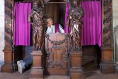 Sinner dans la cabine de confession Photographie stock