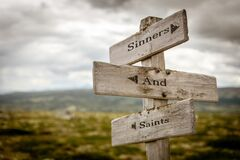 sinners and saints text engraved on old wooden signpost outdoors in nature