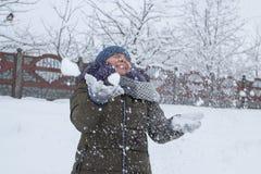 Sinnesrörelseflickan kastar snöboll, en kvinna gör undanflykter kastar snöboll, lyckliga vinterlekar arkivbilder