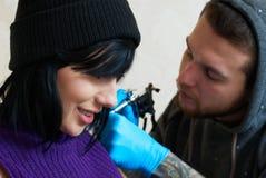 Sinnesrörelser av en flicka, medan göra en tatuering Arkivfoto