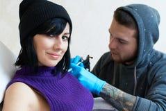 Sinnesrörelser av en flicka, medan göra en tatuering Royaltyfri Bild