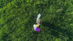 Sinnesrörelser av lycka, den flyg- sikten av tonåringen rotera med ballonger i parkera på solig dag arkivfilmer