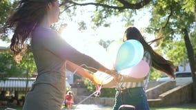 Sinnesrörelser i panelljus, lyckliga flickvänner som rymmer händer som rotera med färgrika ballonger parkerar in, på bakgrundsträ stock video