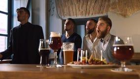 Sinnesrörelserna av fyra vänner som hurrar för deras favorit- lag Reaktionen på dess förlora Den suddiga maten lager videofilmer