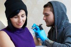 Sinnesrörelser av en flicka, medan göra en tatuering Arkivbild