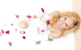 Sinnliche anziehende kaukasische blonde Frau in der schäumenden Badewanne gefüllt mit den blumigen Blumenblättern während der Hau Stockfoto