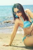 Sinnliche Bikinifrau auf dem Seestrand mit Sonnenbrille Lizenzfreie Stockfotos