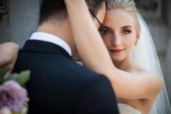 Sinnliche blonde Braut, die starken Bräutigam, Gesichtsnahaufnahme umarmt Lizenzfreie Stockfotografie