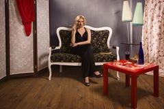 Sinnliche blonde Dame im Schwarzen Stockfotos
