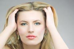 Sinnliche blonde Frau, die goldene Schmucksachen hat Stockbilder