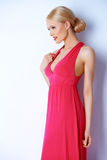 Sinnliche blonde Frau, die im rosa Kleid aufwirft Lizenzfreies Stockfoto