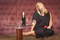 Sinnliche blonde Frau, die nahe Champagne und Rose sitzt Stockfotografie