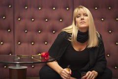 Sinnliche blonde Frau, die nahe Champagne und Rose sitzt Stockfotos