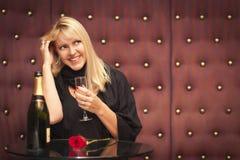 Sinnliche blonde Frau, die nahe Champagne und Rose sitzt Lizenzfreie Stockfotos