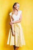 Sinnliche blonde Frau im gelben Rock, der unten schaut Lizenzfreie Stockbilder