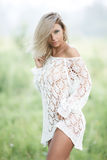 Sinnliche blonde Frau im weißen Kleid draußen Stockfoto