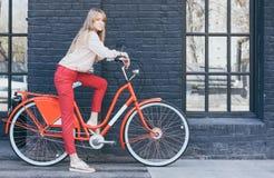 Sinnliche blonde Mädchenaufstellung der Junge recht im Freien mit rotem Weinlesefahrrad in einer roten Chinos-Hose in den Goldtur Lizenzfreie Stockfotografie