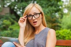 Sinnliche Blondine, die auf Holzbank im Park sitzen Sie ist usi lizenzfreies stockbild