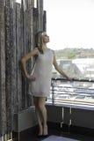 Sinnliche Blondine, die auf städtischem Balkon aufwerfen Stockfotografie