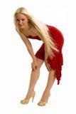 Sinnliche Blondine im roten Verbiegen und im Lächeln Stockfotos