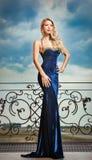 Sinnliche Blondine mit blauem Kleid auf Leiste stockfoto
