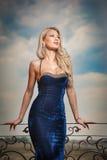 Sinnliche Blondine mit blauem Kleid auf Leiste Stockfotos