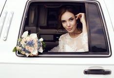 Sinnliche Braut mit dem dunklen Haar im luxuriösen Hochzeitskleid, das im Auto aufwirft Stockfotografie