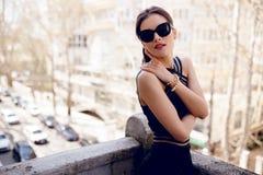 Sinnliche, brunette Frau in der Sonnenbrille, sexy schwarzes Kleid, Haarpferdeschwanz und schönes Gesicht stockfotos