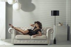 Sinnliche Brunettedame, die an der Luxuscouch liegt lizenzfreie stockbilder