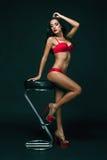 Sinnliche Brunettefrau mit dem perfekten Körper, der in der Wäsche, Rotrose halten aufwirft Stockbilder