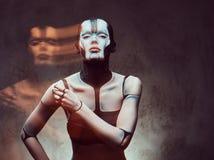 Sinnliche Cyberfrau mit kreativem Make-up Technologie- und Zukunftkonzept Lokalisiert auf einem dunklen strukturierten Hintergrun stockfoto