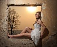 Sinnliche Dame im weißen Kleid, das zum Fenster und zur roten Sonne hinter ihr schaut Lizenzfreies Stockfoto