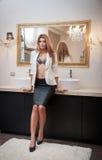 Sinnliche elegante Frau in der Büroausstattung, die vor einem großen Spiegel bleibt. Schöne und sexy blonde junge Frau, die sexy B Stockfoto