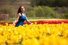 Sinnliche Frau auf dem Blumengebiet am sonnigen Tag Stockfoto