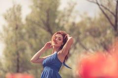 Sinnliche Frau auf dem roten Blumengebiet am sonnigen Tag Lizenzfreies Stockfoto